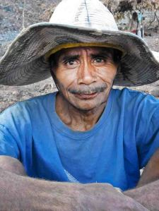 Worker hand-sorting manganese in large mine, West Timor.